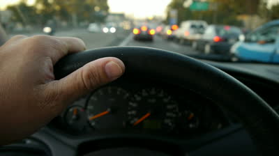 driving-at-sunset-on-the-freeway-traffic-jam-hand-on-steering-wheel-close-up-pov