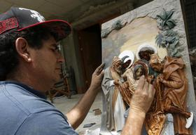 Sculptor Orlando Carranza paints a religious sculpture in his workshop in Atenas